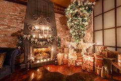 Alternative tree upside down on the ceiling. Winter home decor. Modern loft interior with fireplace and brick wall Royalty Free Stock Image