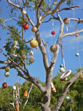 Alternative tropical christmas tree with fishing floats and fenders before blue sky. Tropical alternative christmas tree outdoors decorated with fishing floats Royalty Free Stock Photography
