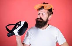 Alternative Wirklichkeit Bemannen Sie bärtigen Hippie mit Kopfhörer der virtuellen Realität und Sonnenbrillerothintergrund mit Lu lizenzfreie stockfotos