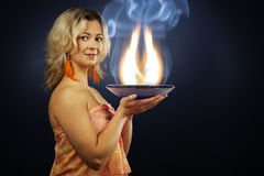 Alternative woman. Woman of esoteric soul holding a pan full of flames describing inner flames of soul royalty free stock images
