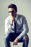 Alternative young business man wearing shirt, tie and ripped jeans Stock Image