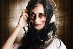 Hard rock zombie listening to death metal music. Alternative zombie girl listening to melodic death metal with earphones when rocking out to the sound of the Stock Image