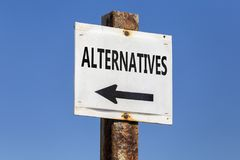 Alternatives word and arrow signpost. On clear sky background. Motivational sign Royalty Free Stock Photography