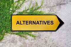Alternatives on yellow sign hanging on ivy wall. Close Royalty Free Stock Photo