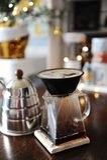 Alternativt manuellt kaffe som bryggar i poröst keramiskt paperless filter Gooseneckkokkärl Oskarpa ljus på bakgrunden arkivbilder