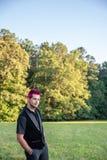 Alternativt olikt manligt - svart kläder, rosa hår som smilar på kameran royaltyfria bilder
