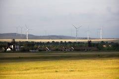 Alternatywna energia, wiatrowych gospodarstw rolnych stojak w polu obok domów Obraz Stock