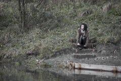 Alternatywny model siedzący na schodkach blisko nawadnia Fotografia Royalty Free