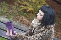 Alternatywny model siedział na ławce z pastylka pecetem Zdjęcia Royalty Free