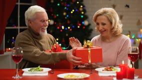 Alternde Paare, die Geschenke auf Weihnachtsabends-Angebotbeziehungen durch Jahre austauschen stock video footage