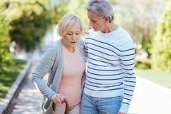 Alternmann, der kranke Frau im Park stützt Lizenzfreie Stockfotos