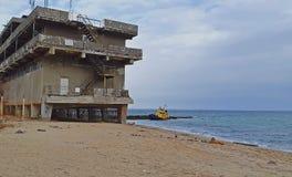 Altes überschwemmtes schleppendes Schiff und das verlassene Gebäude nahe dem Ufer Drastische Ansicht des überschwemmten Bootes na stockbild