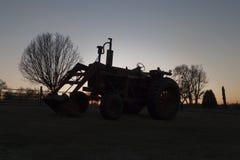 Altes Ackerschlepperschattenbild bei Sonnenuntergang Stockbilder
