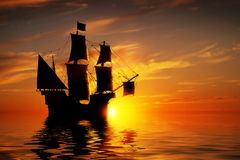 Altes altes Piratenschiff auf ruhigem Ozean bei Sonnenuntergang Stockfotos