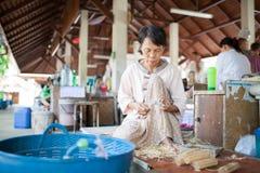 Altes asiatisches Frauensitzen, einen hölzernen Regenschirm herstellend lizenzfreie stockfotografie