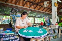 Altes asiatisches Frauensitzen, grüner hölzerner Regenschirm der Malerei stockbild