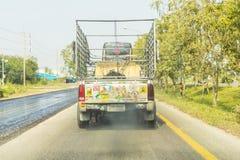 Altes Aufhebung Toyota voll mit den thailändischen Alphabetaufklebern, die auf thailändischer Landstraße laufen und schwarzen Rau stockfotografie