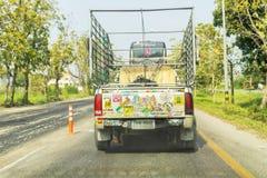Altes Aufhebung Toyota voll mit den thailändischen Alphabetaufklebern, die auf thailändischer Landstraße laufen und schwarzen Rau stockfoto