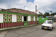 Altes Auto in einer Straße der Stadt von Salento, in Kolumbien, mit einem alten bunten Kolonialhaus Stockbild