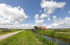 Altes Bauernhaus durch Fluss über blauem Himmel lizenzfreie stockfotografie