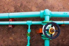 Altes blaues Rohr des Ventils und des Wassers auf dem Boden Stockfotos