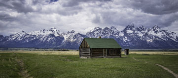 Altes Blockhaus auf dem grünen Gebiet mit großartigem Tetons-Berg Lizenzfreies Stockfoto