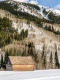 Altes Blockhaus im Winter vor am Berg Lizenzfreies Stockfoto