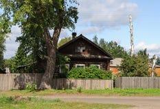 Altes Blockhaus mit einem großen Baum in der Front Stockbild