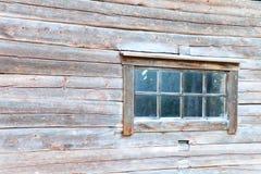 Altes Blockhausfenster mit rustikalem Rahmen Stockfoto