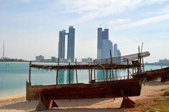 Altes Boot auf dem Hintergrund von Wolkenkratzern in Abu Dhabi Lizenzfreies Stockbild