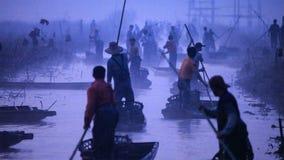Altes Boot der chinesischen Mannreihen durch die Anwendung des langen Stockes yunnan China lizenzfreie stockbilder