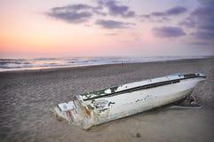 Altes Boot im Sand am Sonnenuntergang Stockbilder