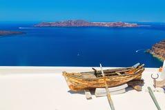 Altes Boot mit Rudern auf hellem weißem Dach Tiefes blaues Meer und Vulkaninsel auf dem Hintergrund Santorini, Griechenland lizenzfreie stockbilder