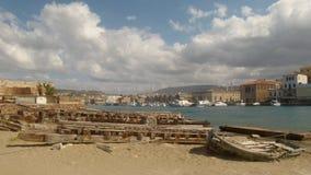 Altes Bootsausbreiten und -Passage liegend auf dem Sand vor dem hintergrund der Promenade von Chania stockfotografie