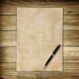 Altes braunes Papier und Stift auf hölzernem Wandhintergrund für Beschaffenheit Stockfotografie
