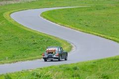 Altes britisches Autofahren auf S-gebogene Straße Stockbild
