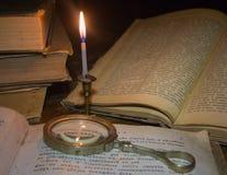 Altes Buch auf einem Holztisch durch Kerzenlicht Stockfotos