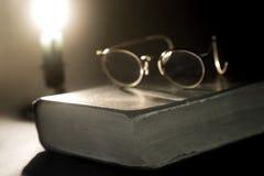Altes Buch beleuchtet durch Kerze Lizenzfreie Stockbilder