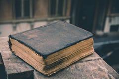 Altes Buch der Weinlese auf Stein, Schmutz maserte Abdeckung Retro- angeredetes Bild mit unscharfem Hintergrund Lizenzfreie Stockbilder