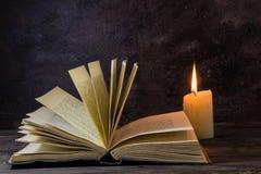 Altes Buch durch candlight mit dem Auflockern von Seiten Stockfotos