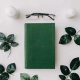 Altes Buch, Gläser, Grün verlässt auf weißem Hintergrund Flache Lage Stockfotos