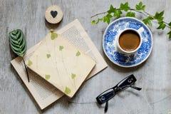Altes Buch, Gläser, Tasse Kaffee und ein Umschlag auf dem Tisch Weinlese-noch Leben Stockbild