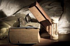 Altes Buch mit Augenglas und Stundenglas stockfotografie