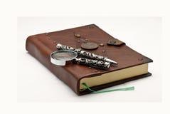 Altes Buch mit einer Feder und einem Vergrößerungsglas stockfotografie