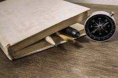 Altes Buch mit Kompass Lizenzfreie Stockfotografie