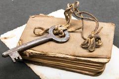 altes Buch, rostiger Schlüssel und leere Fotografie Stockbilder