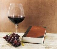 Altes Buch und Rotwein mit Trauben auf Tabelle Lizenzfreie Stockbilder