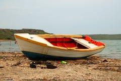 altes buntes gemaltes Boot auf einem Strand Stockfotografie
