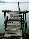 Altes Dock, das in nebeliges Wetter mit der Stadt oben zeigt im Hintergrund schwimmt stockfotos