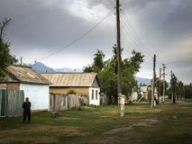 Sleepy old village in the morning, power lines, gray clouds royalty free stock images